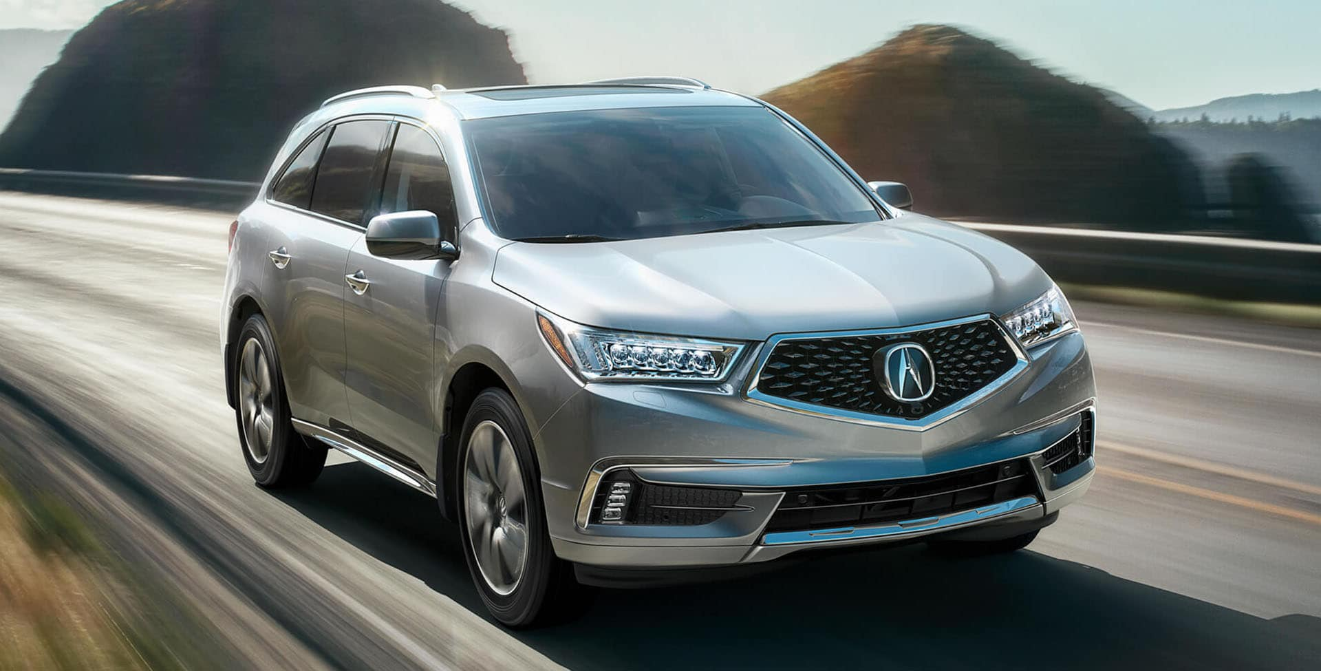 Silver Acura MDX driving through mountains