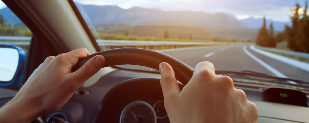 driver hands on steering wheel with open highway woods and mountains ahead