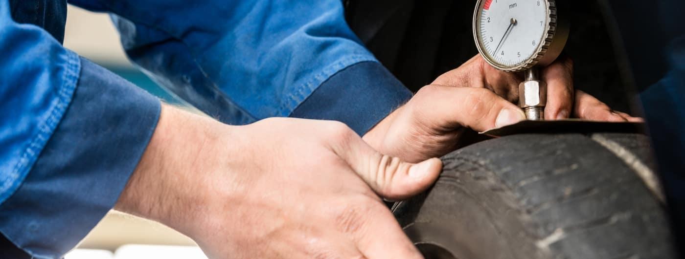 Hands Of Mechanic Pressing Gauge Into Tire In Garage