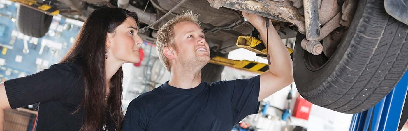 mechanic-and-woman-looking-under-automobile-6478315_xl-2015