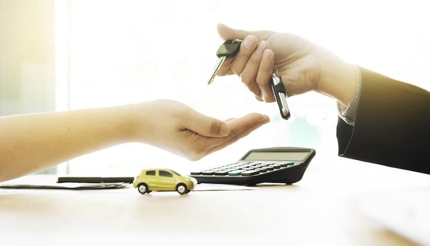 Handing over the keys to another person, with a calculator in the background