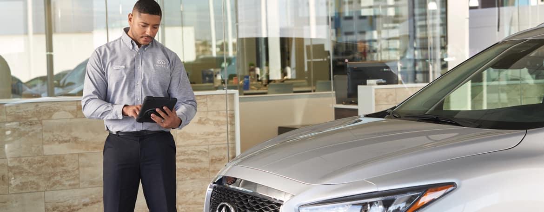 INFINITI Sales associate reviewing vehicle in dealership showroom.