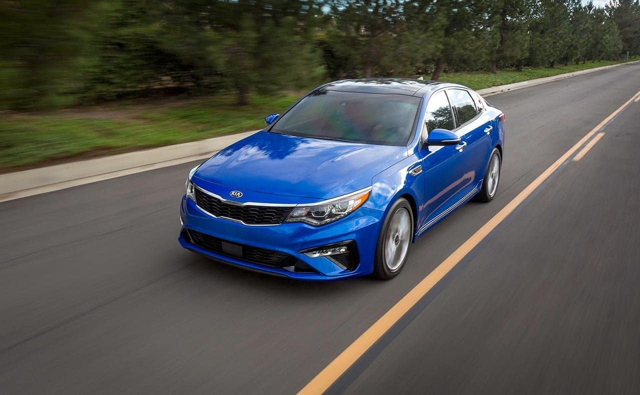 2019 Kia Optima in blue driving down the road