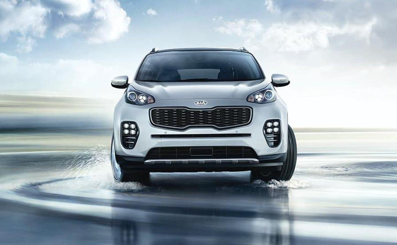 2019 Kia Sportage in silver drifting on road with water