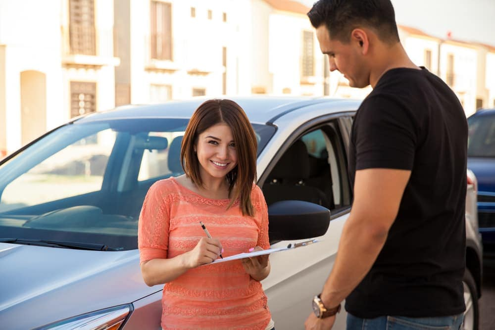 Woman signing financial paperwork for car