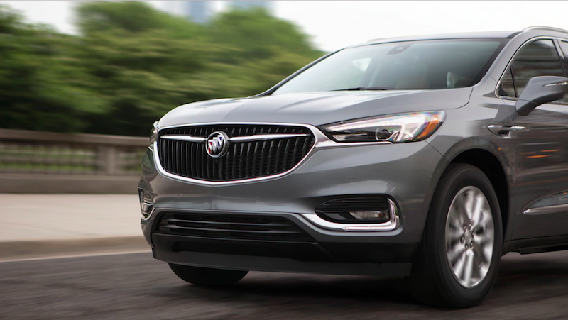 Gray Buick Enclave driving down a road