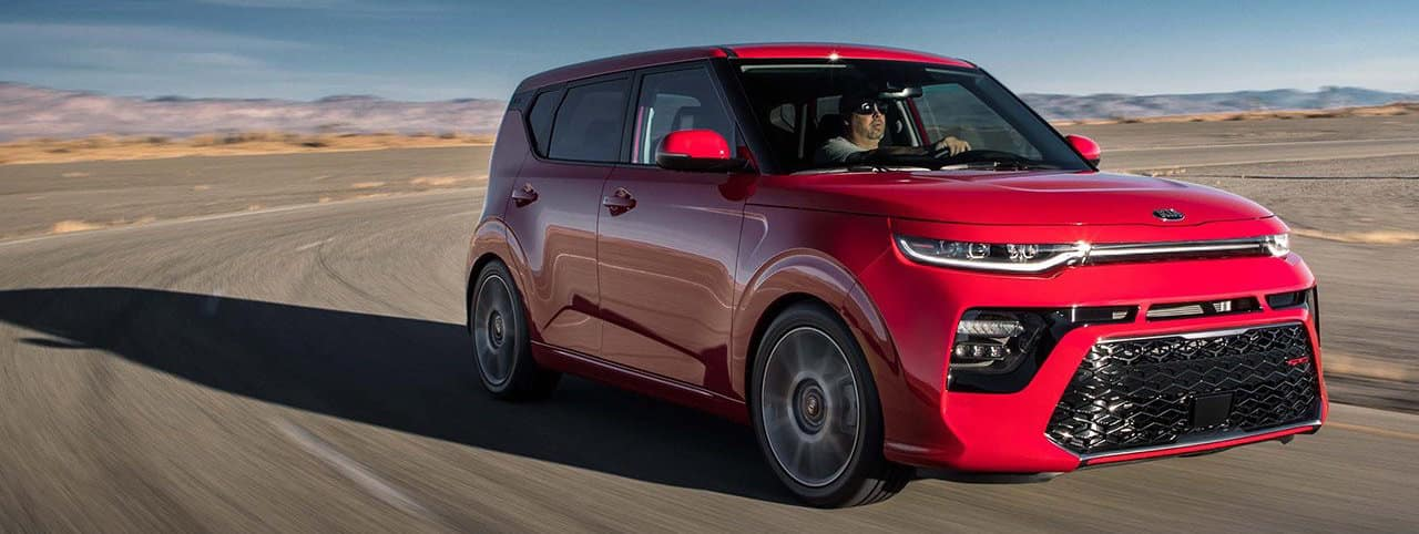 Red Kia Soul driving on a road in the desert