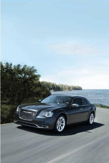 black chrysler 300 driving near ocean on sunny day