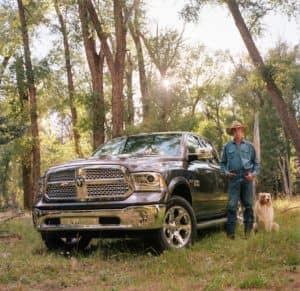 Man with cowboy hat standing next to blue ram and dog in woods