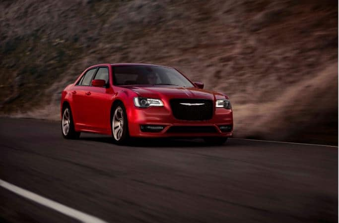 red chrysler 300 driving down highway