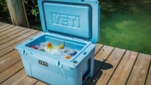 Light Blue Yeti Cooler with ice and variety of drinks in cooler on light brown dock with water in background