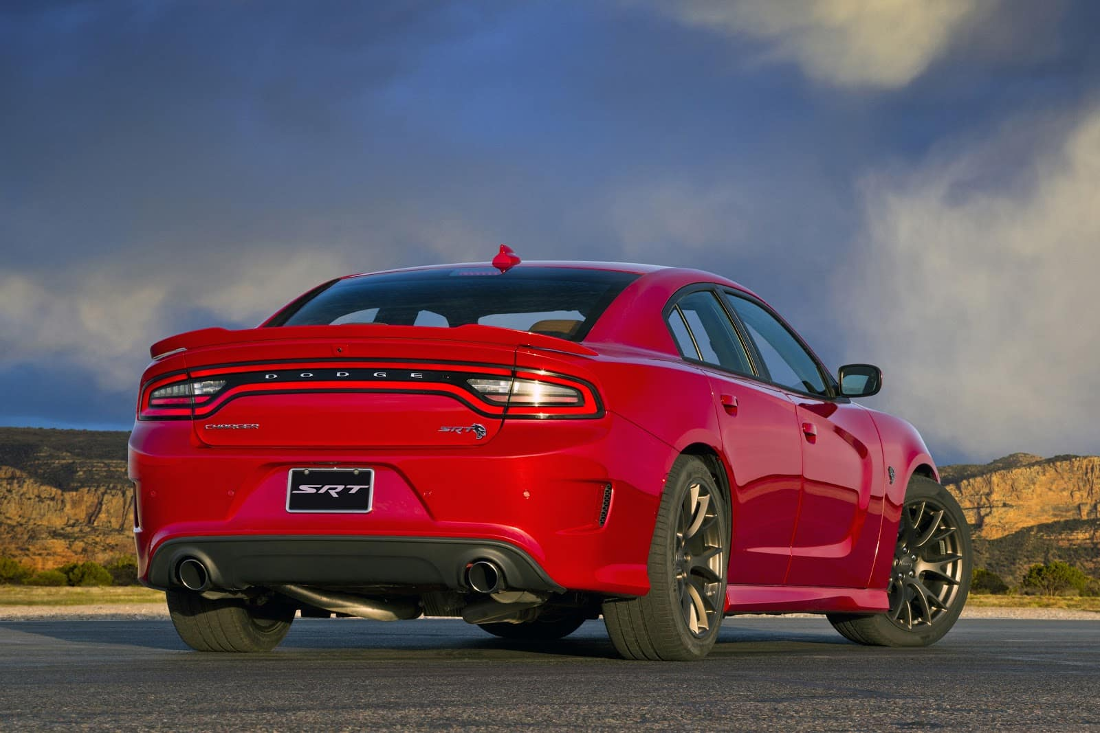 Red 2019 dodge charger SRT with bumper facing user with mountains and canyons in background
