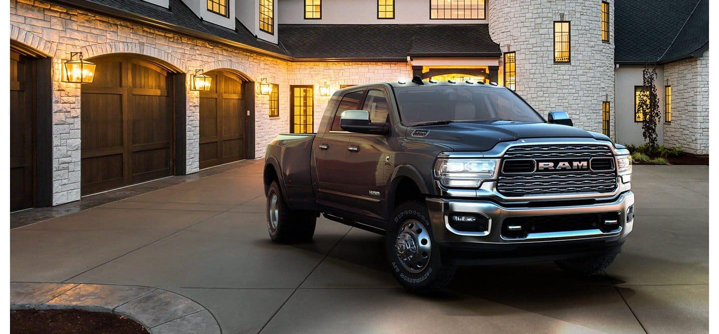 black ram 3500 parked outside luxurious exterior of house with porch lights surrounding