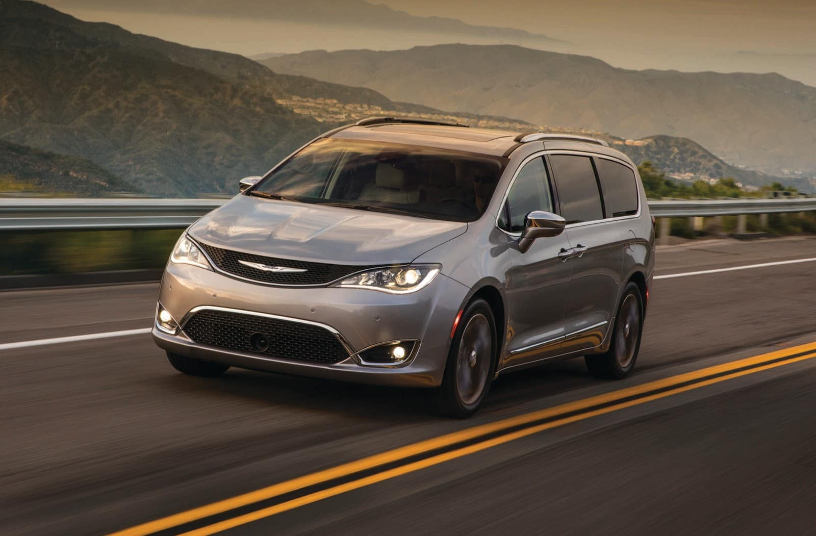 silver 2019 chrysler pacifica driving on winding highway with mountains in background