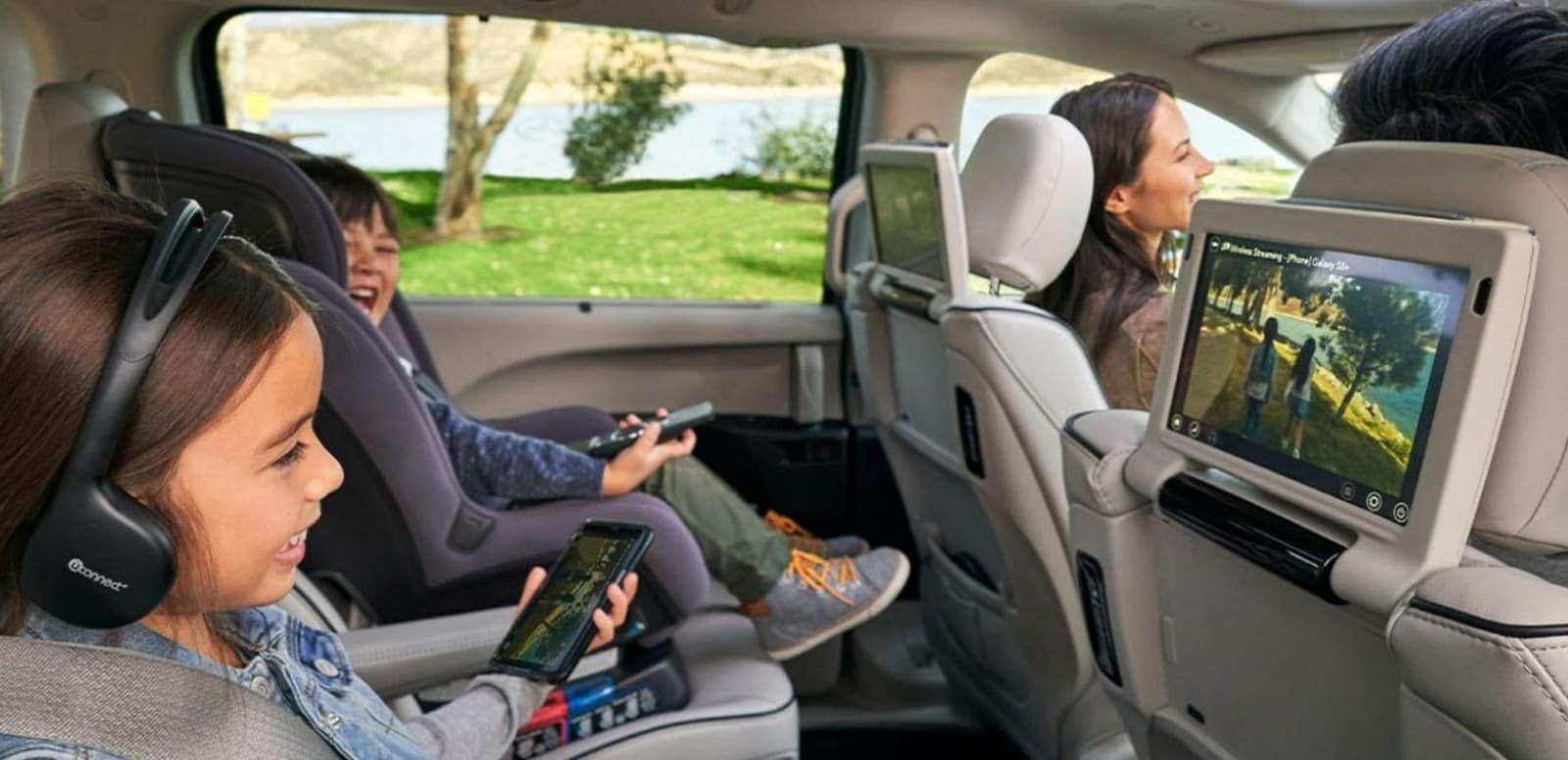 kids in backseat of 2019 chrysler pacifica watching tv on back of seat with headphones and holding smartphone while mom drives