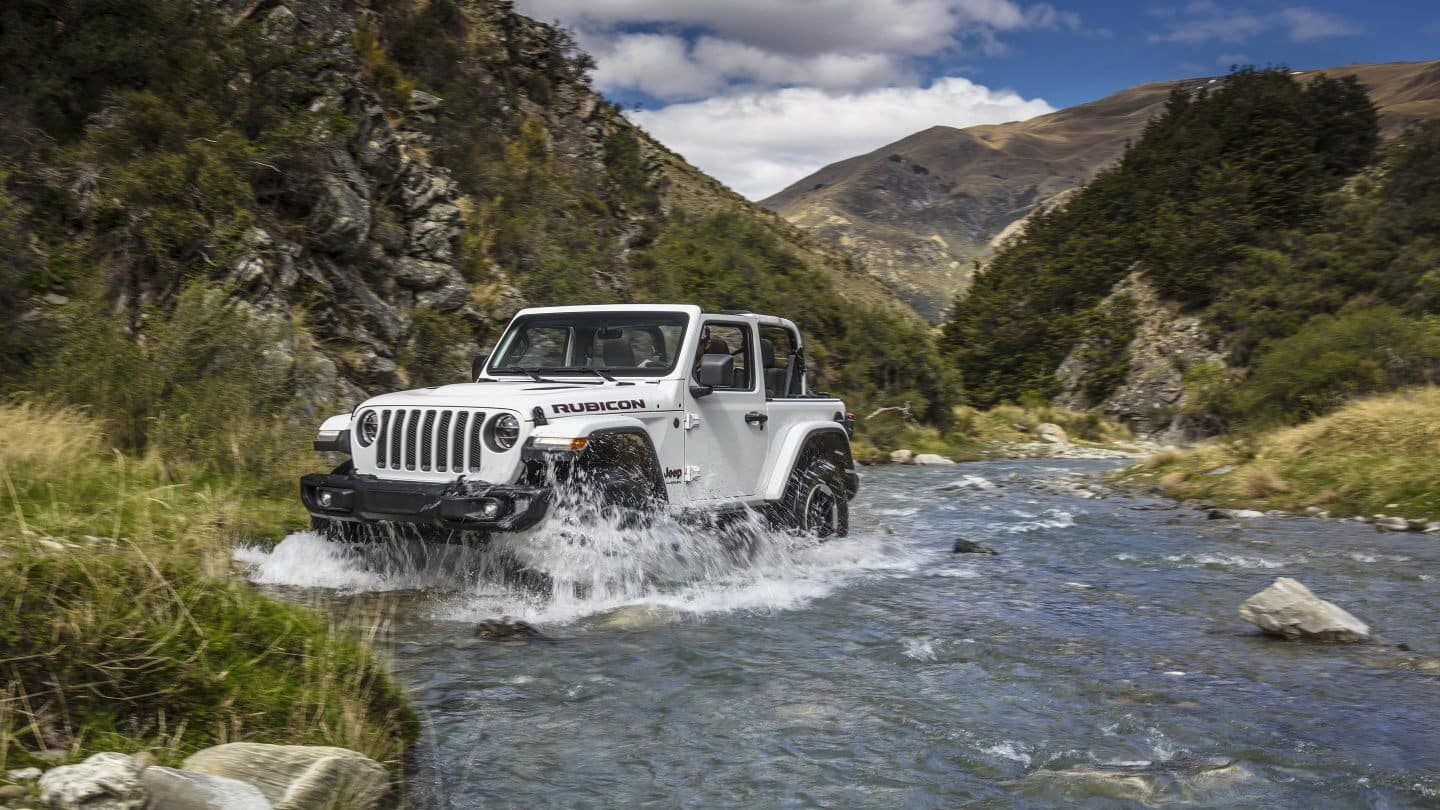 white jeep wrangler going thru creek filled with water inbetween mountains