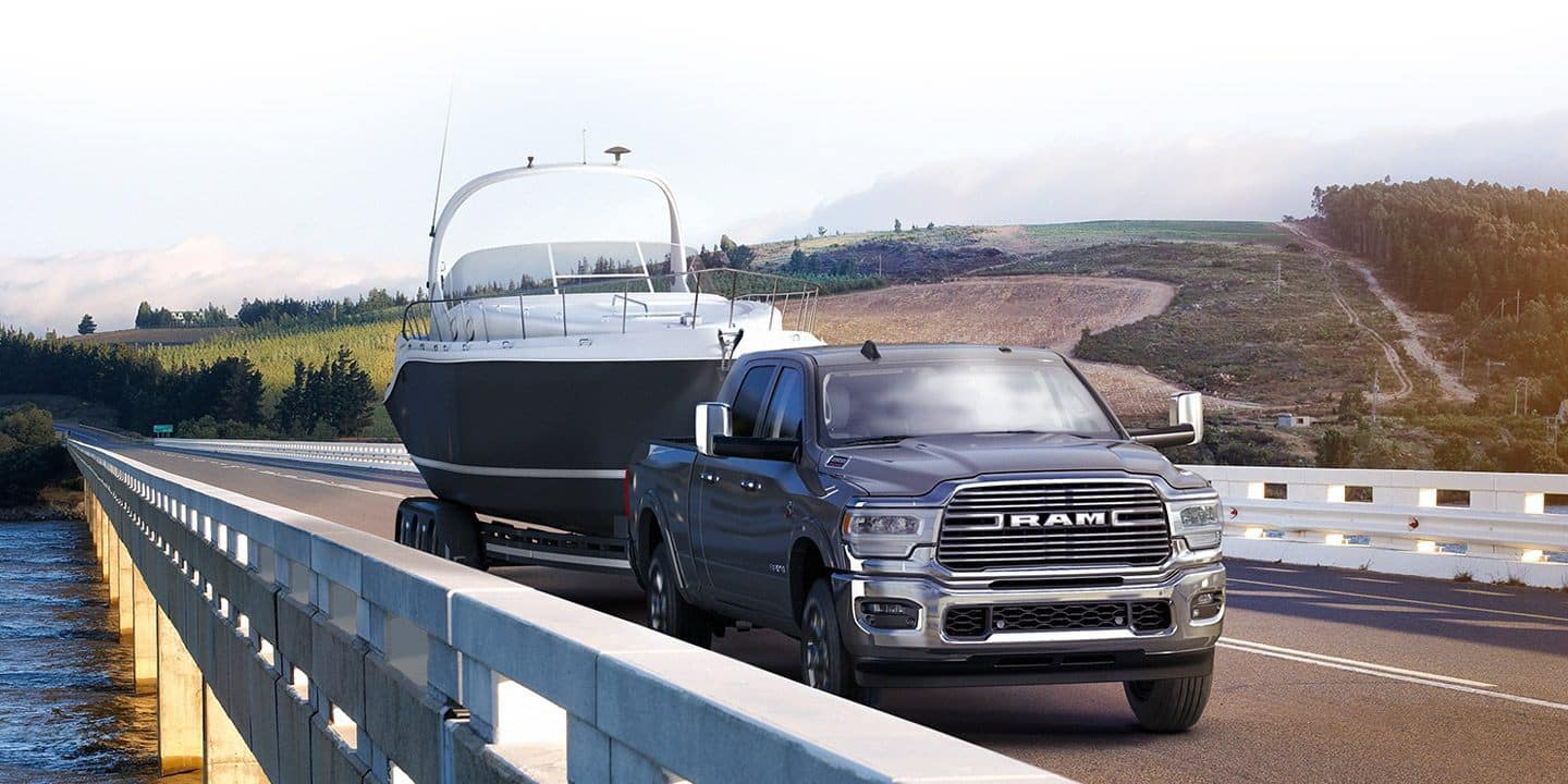 ram 2500 towing a boat on bridge over lake
