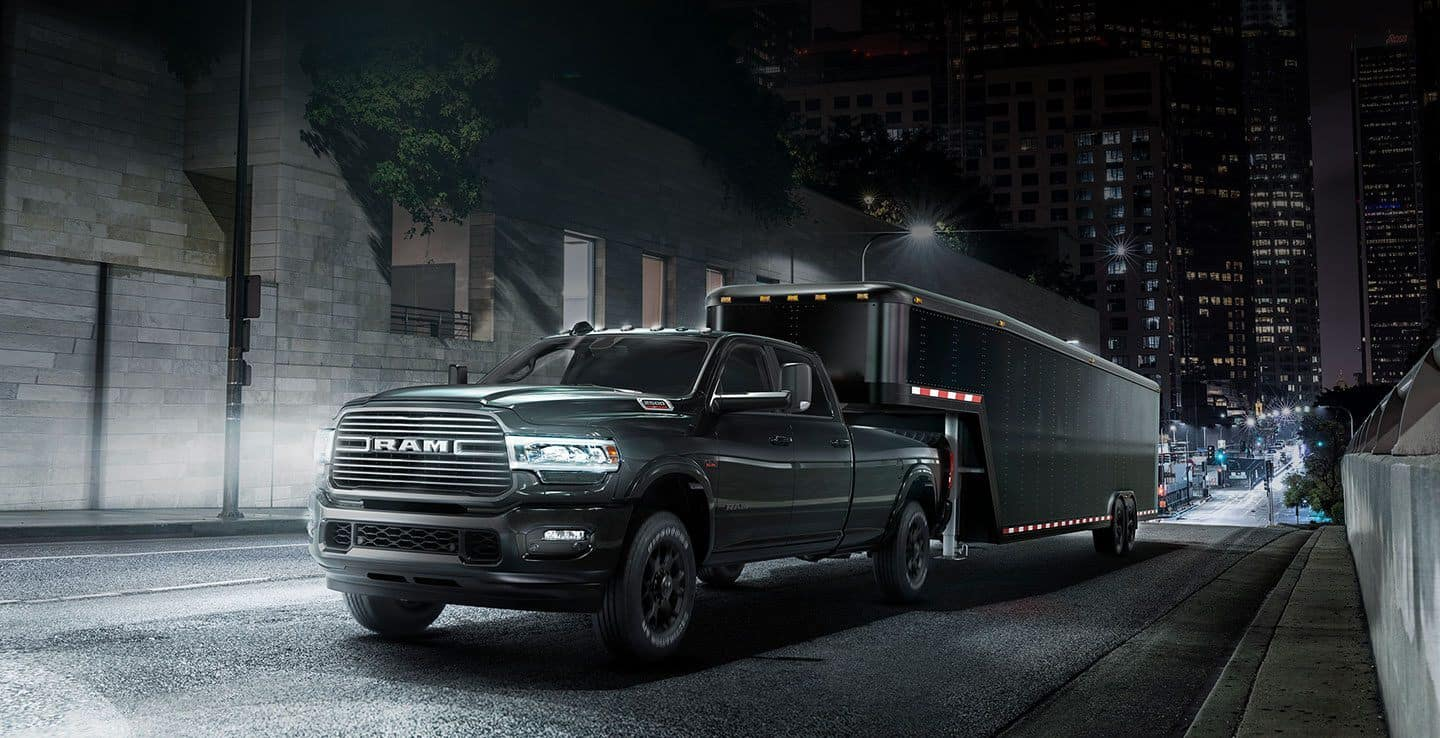 black ram 2500 towing a black trailer surrounded by city lights and streets