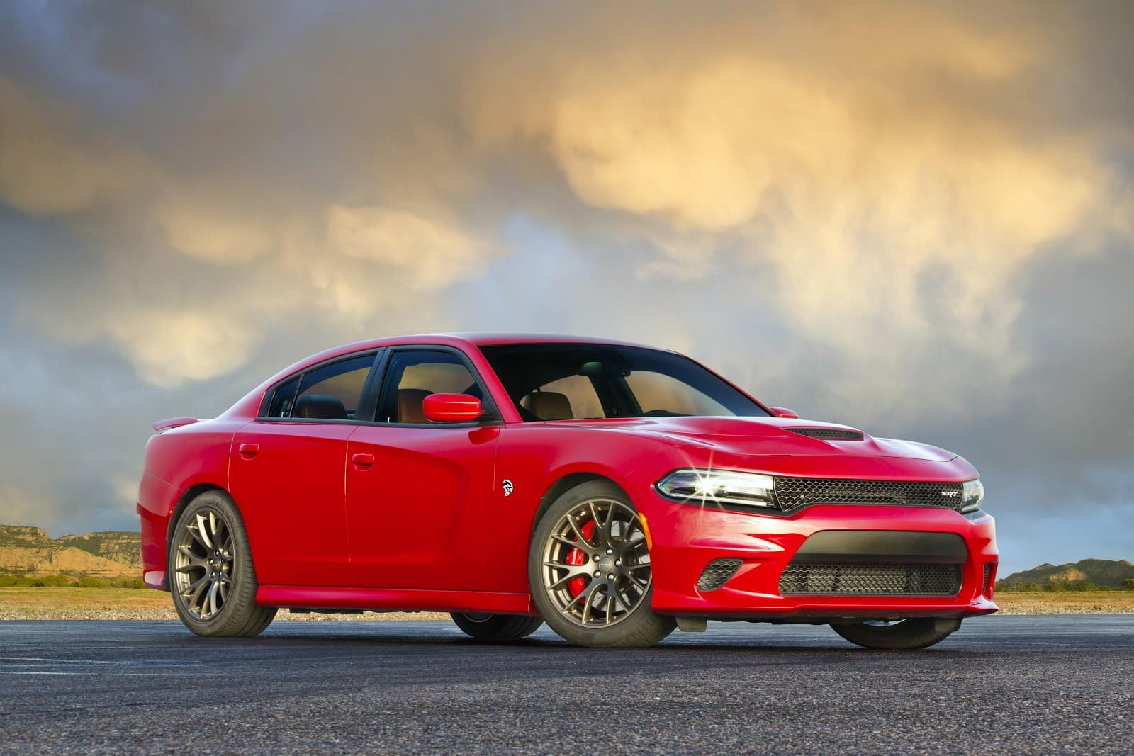 red 2019 dodge charget srt parked sideways on asphalt with sunset in the background