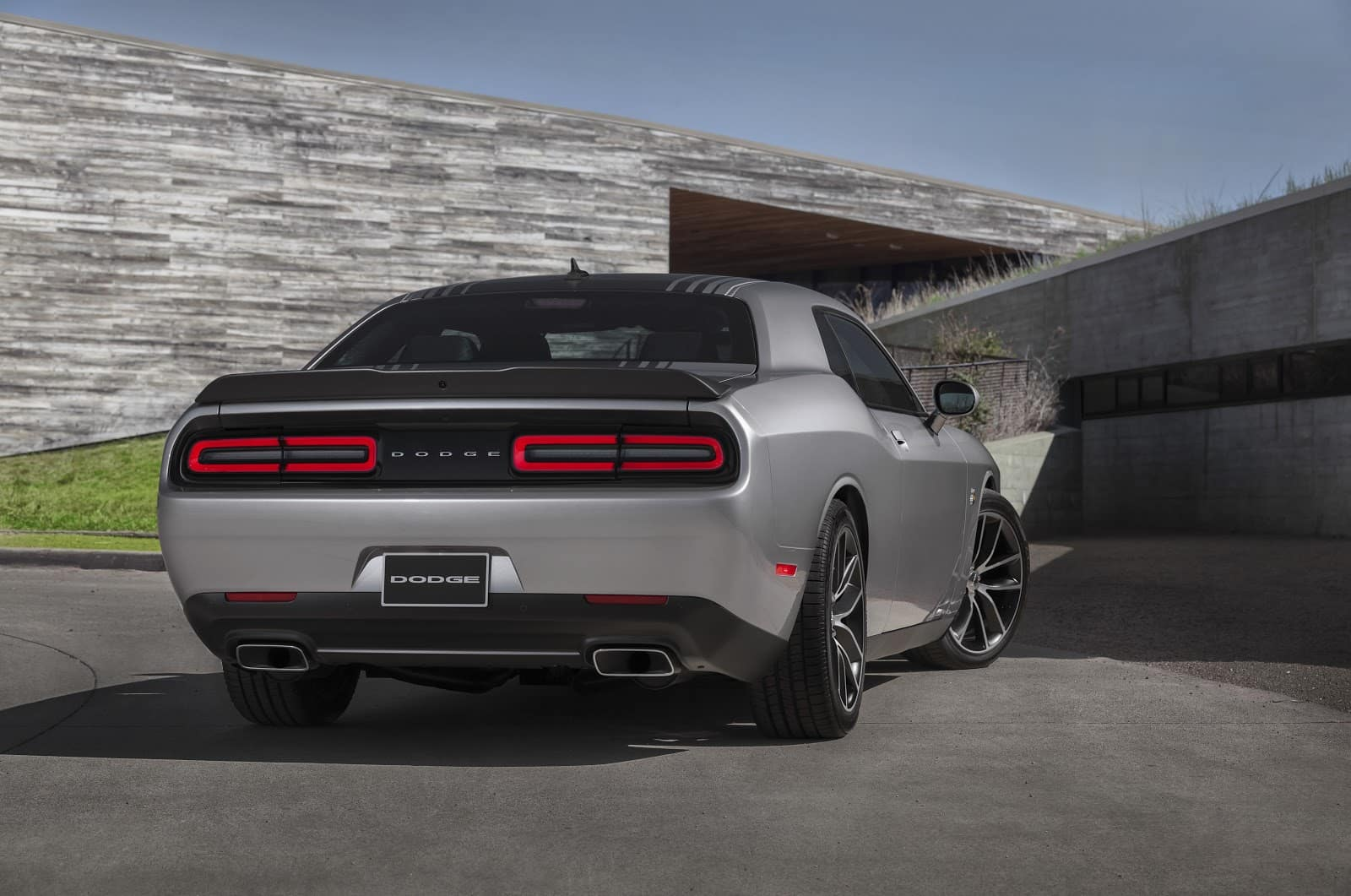 silver dodge challenger parked against concrete exterior of house