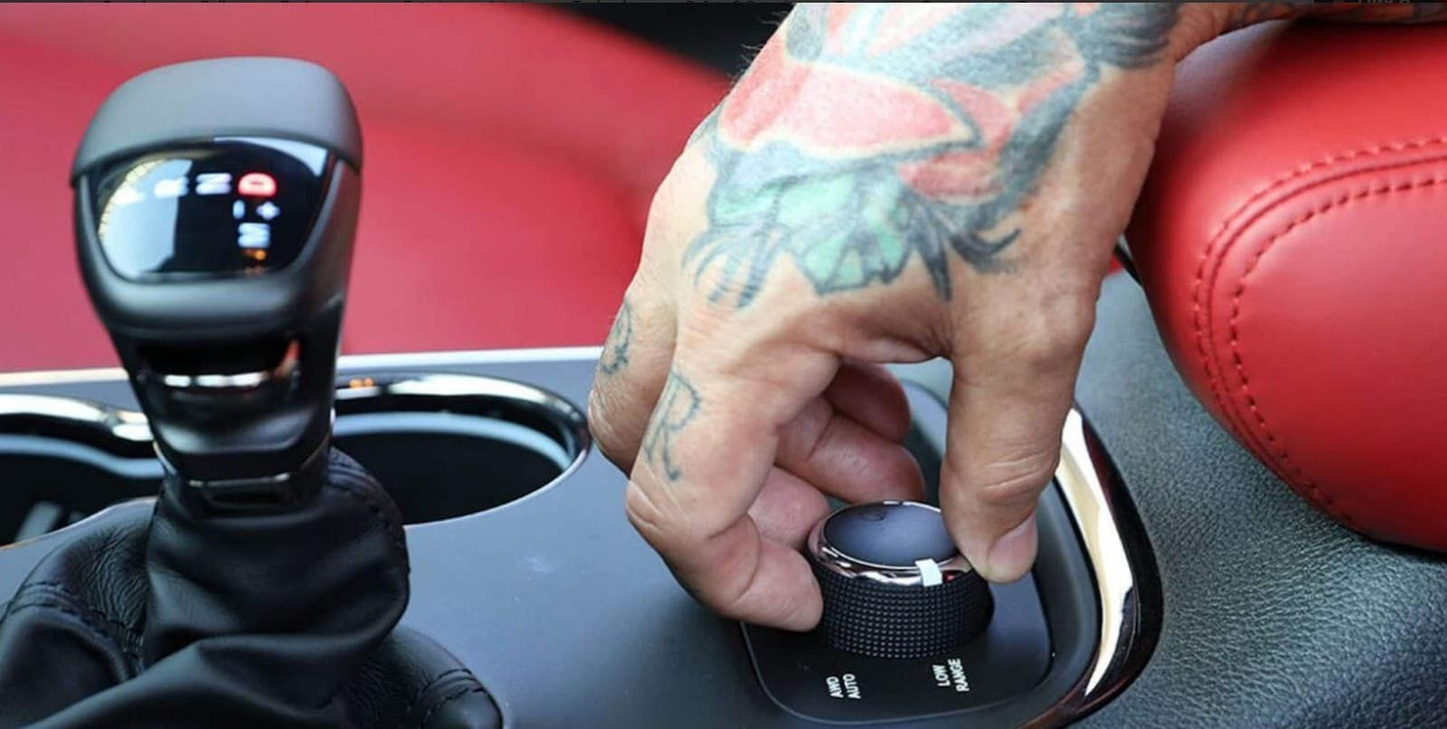 tattooed hand holding knob on dodge durango srt against bright red interior
