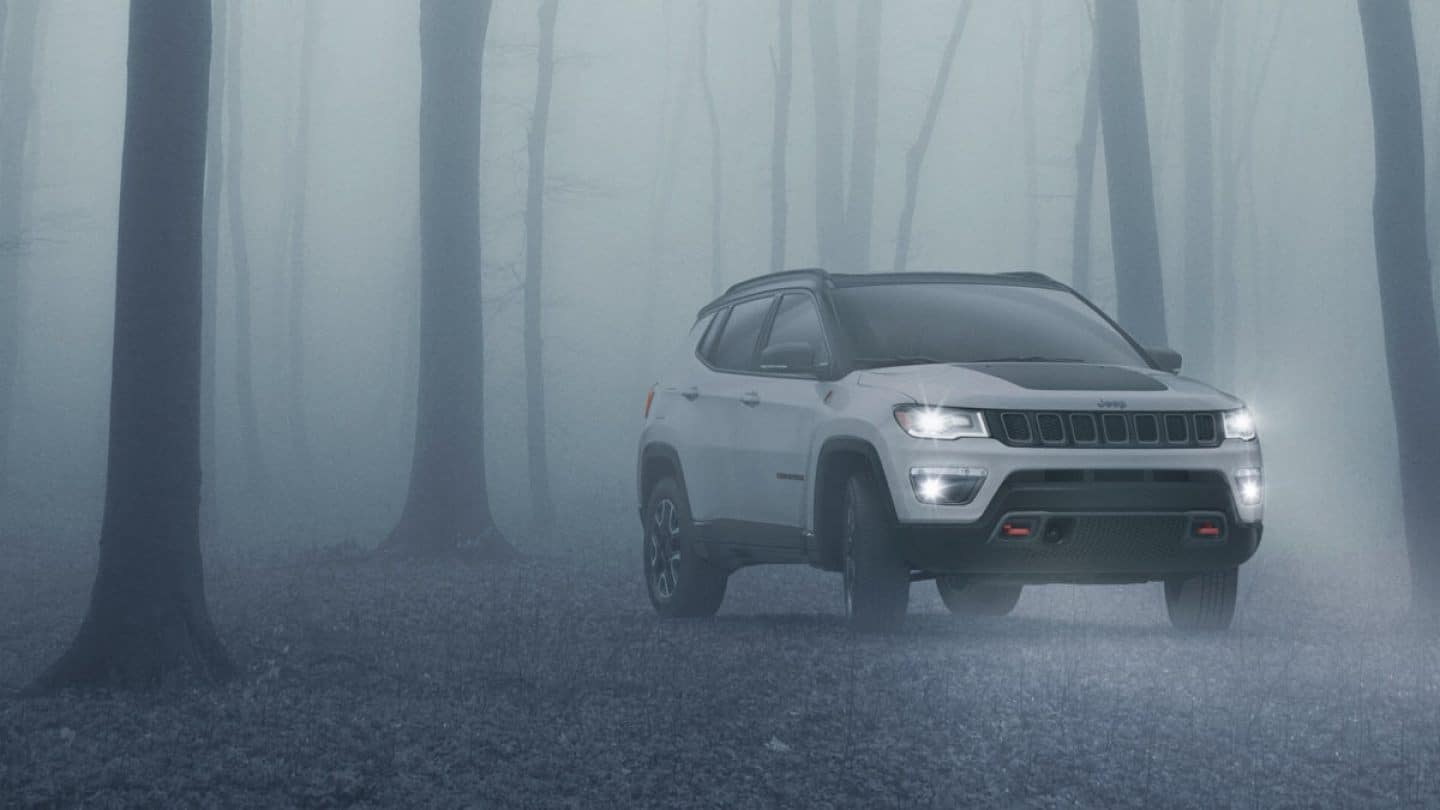white jeep compass in fog in forest