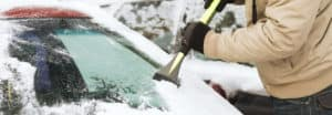 scraping snow off of a cold windshield