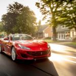Woman driving Ferrari through a neighborhood