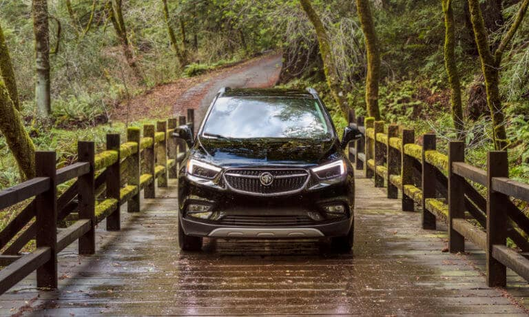 Front view of a Black 2020 Buick Encore in a forest