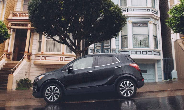 Black 2020 Buick Encore parked on a street outside some houses in the rain