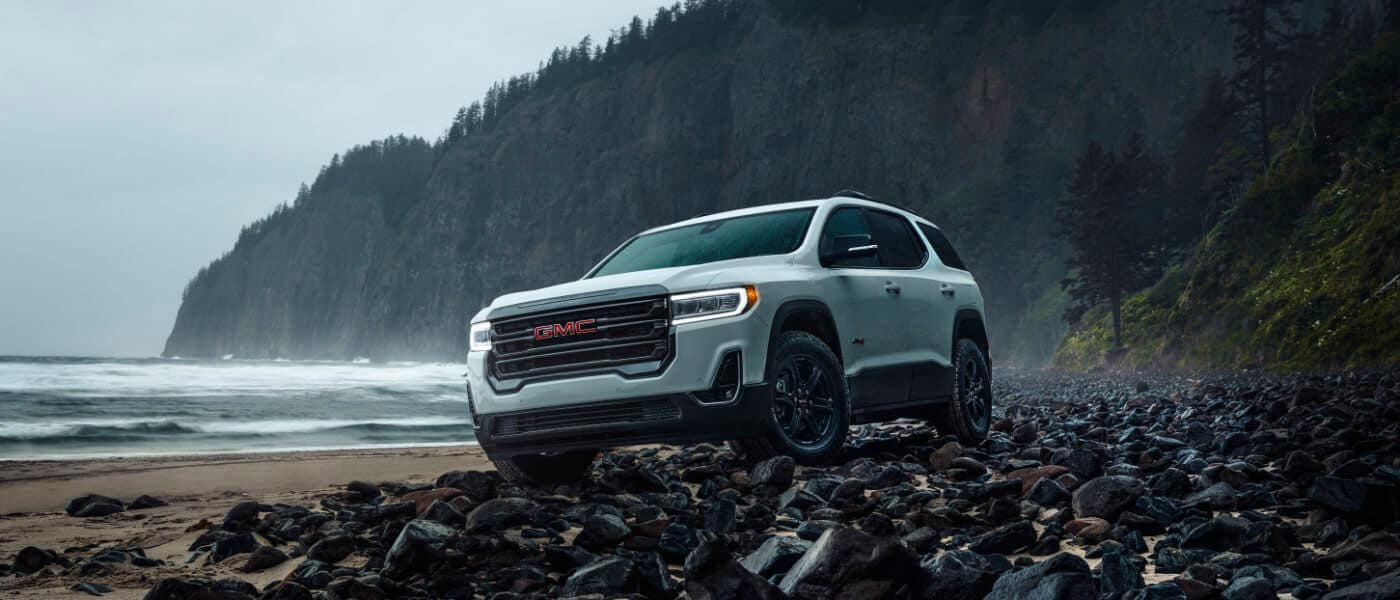 White 2020 GMC Acadia on a beach by a lake