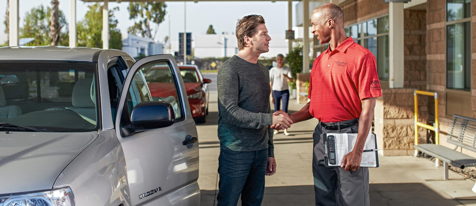 New Car Alternative at Hartford Toyota | Sales Advisor Shaking Hands with Customer Next to a Toyota Tacoma