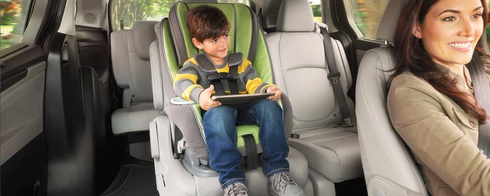 Child using tablet in back seat of a Honda minivan