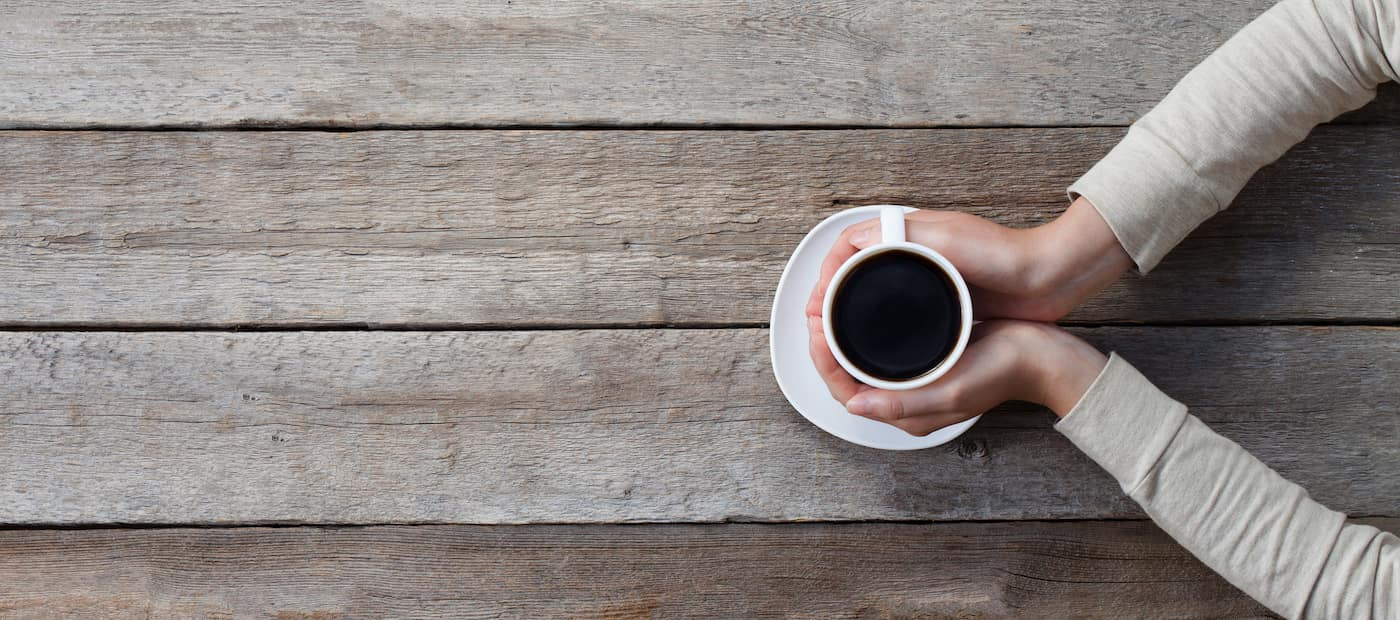 woman hands holding mug of hot coffee cup that standing on wooden table