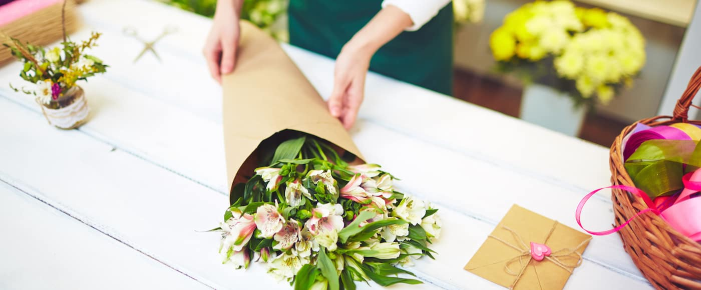 Female florist selling bouquet of amaryllises
