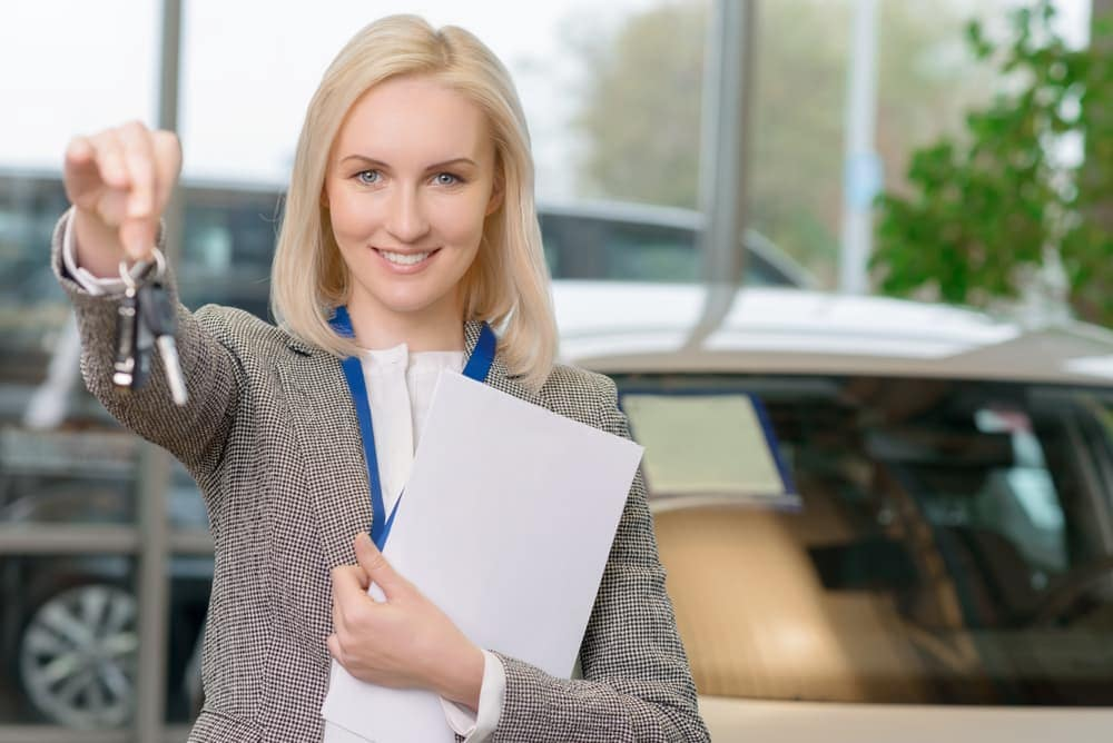 Female sales associate holding car keys