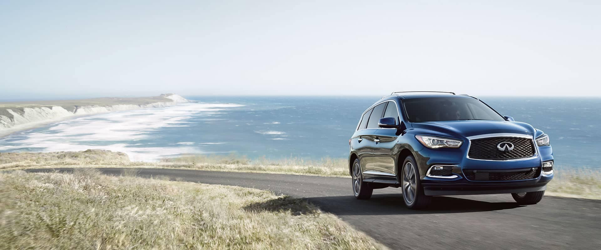 INFINITI QX60 driving down curved road