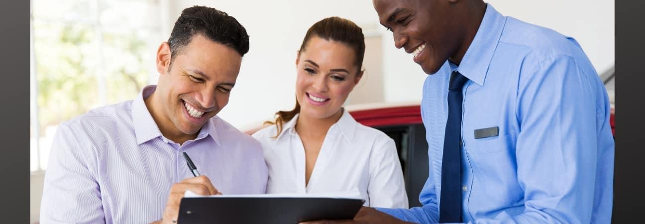 Dealership staff discussing financing vs. leasing