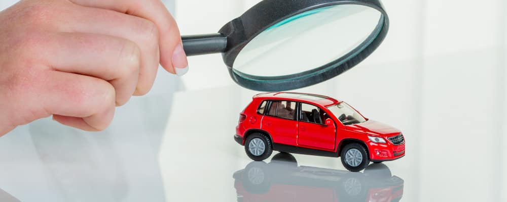 An small SUV underneath a magnifying glass, being inspected for issues which may fall under a Kia warranty.