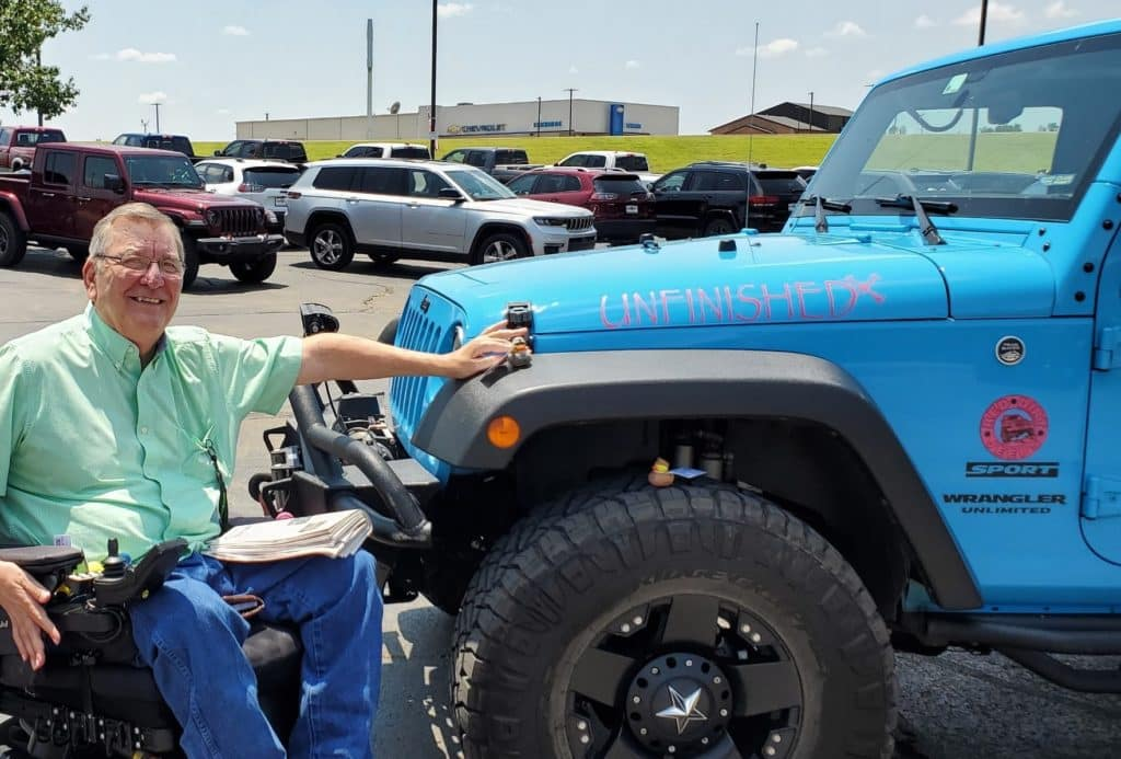 a photo of Bill in front of a blue jeep Wrangler in Guthrie, Oklahoma