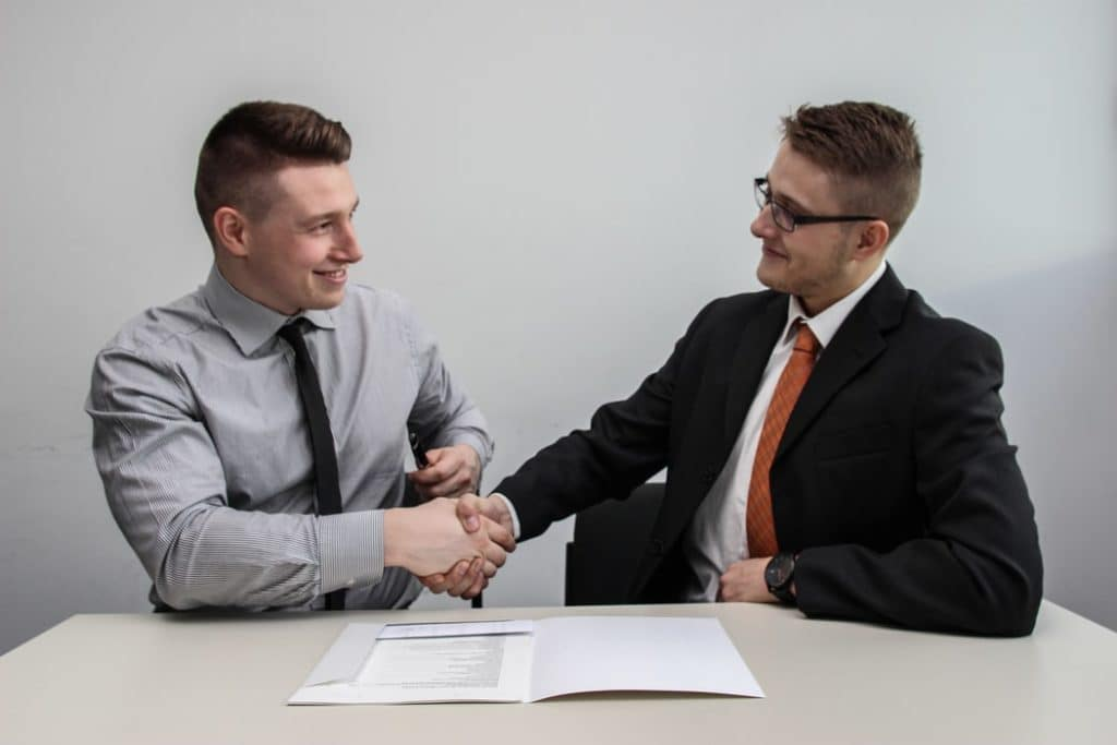 two people shaking hands while smiling inside a dealership