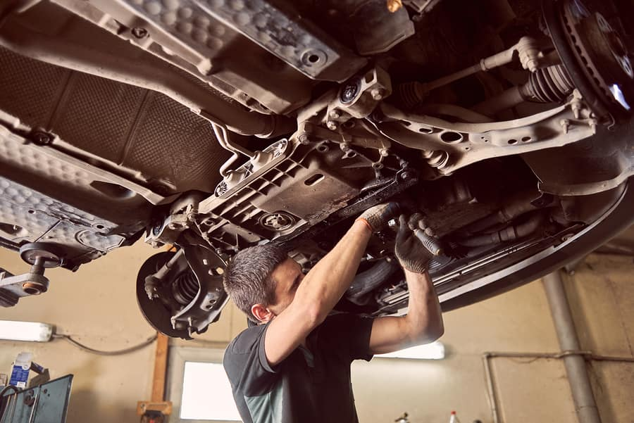 a local mechanic repairing the underside of a car