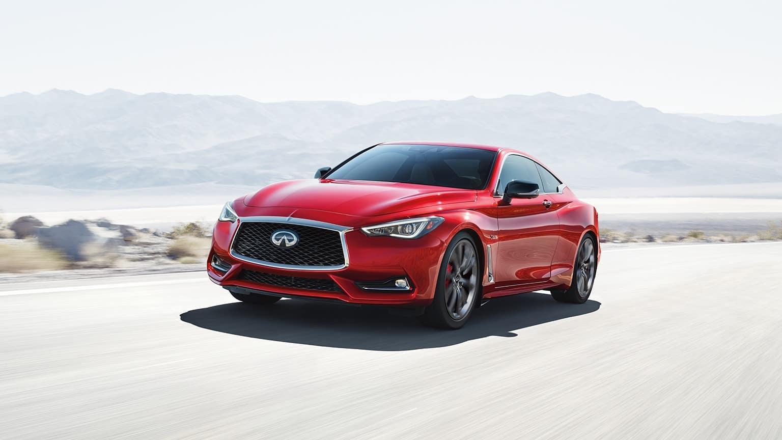 Red 2020 INFINITI Q60 Sport driving down a desert highway