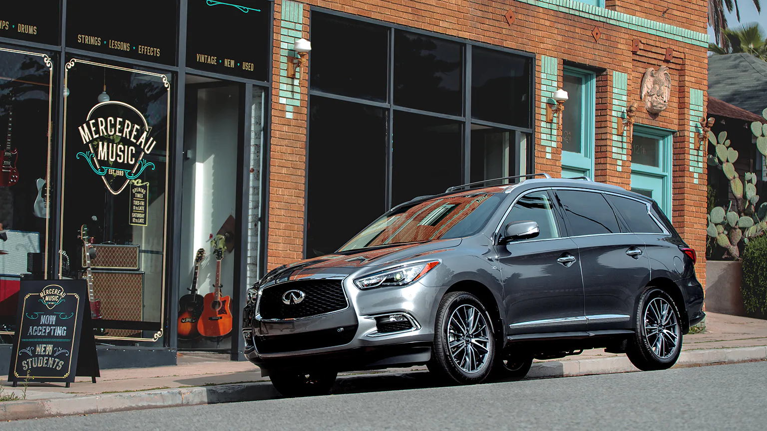 Gray 2020 INFINITI QX60 parked in front of a brick building. Available now at Kearny Mesa INFINITI.