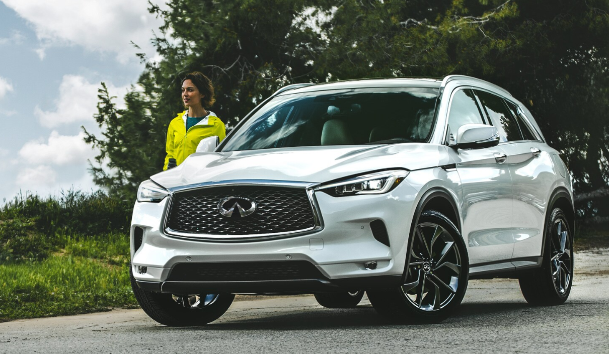 Woman standing next to a white 2020 INFINITI QX60. Available now at Kearny Mesa INIFINITI of San Diego