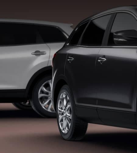 Partial view of 2 vehicles, one black and one silver