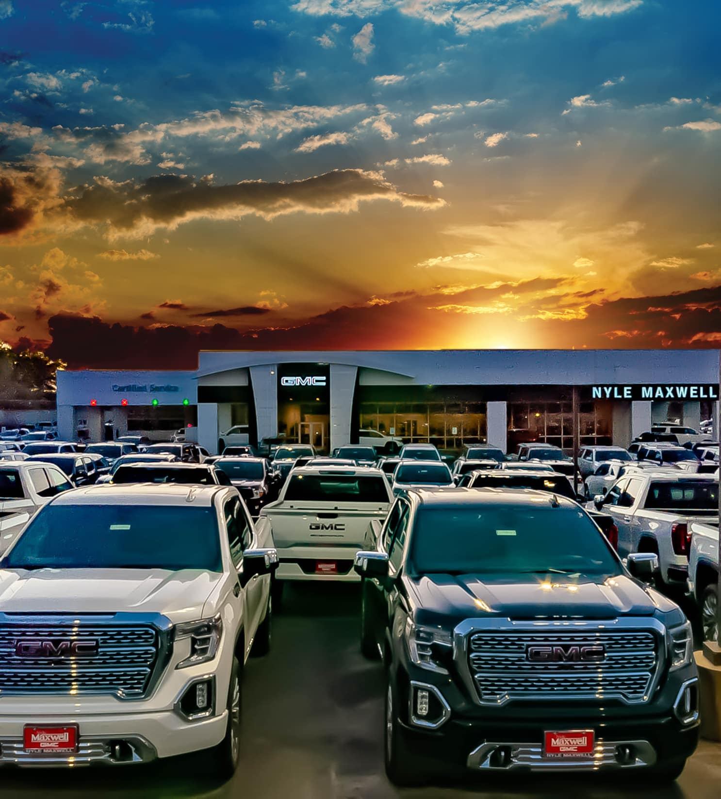 Nyle Maxwell GMC homepage SEO image - GMC trucks parked in the foreground in front of Nyle Maxwell GMB