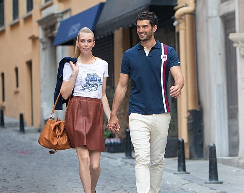 Young couple walk through a European city wearing their Volkswagen-branded clothes and accessories.