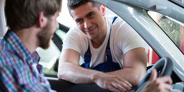 A bearded man in a plaid shirt sits in the driver seat of his car with his window open. A muscular man wearing a tight, white t-shirt and blue overalls leans into the vehicle through the driver-side window, resting his arms on the windowsill. He smiles and locks eyes with the driver.