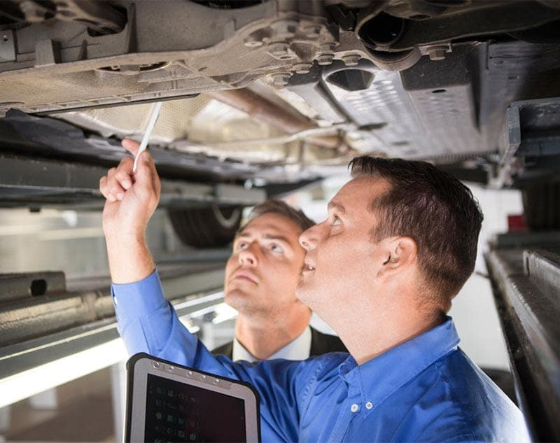 A technician in a blue shirt points at something in the undercarriage of a vehicle. A scowling man in a black business suit looks at whatever the technician is pointing to.